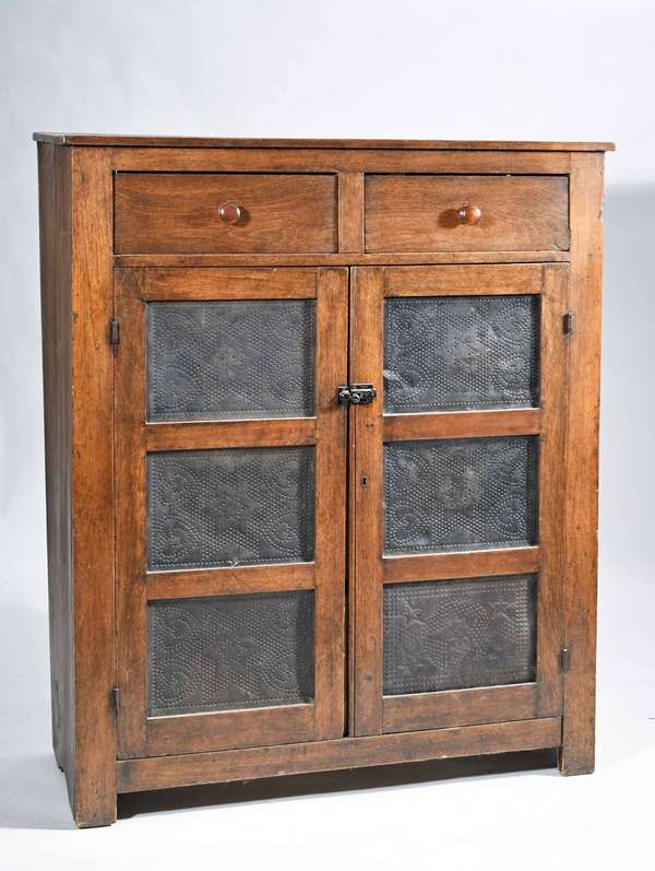 "LATE 19TH C. WALNUT TWO-DOOR PIE SAFE. The front doors with heart and star design punched tin panels, with two upper pull drawers of dovetailed construction; fitted with two interior shelves, 51 1/4"" H x 44"" W x 16 1/4"" D. Condition: Replaced pull drawer knobs and lock hardware on door.  Large shrinkage cracks on top proper right back side. Chip and repair to proper left back foot."