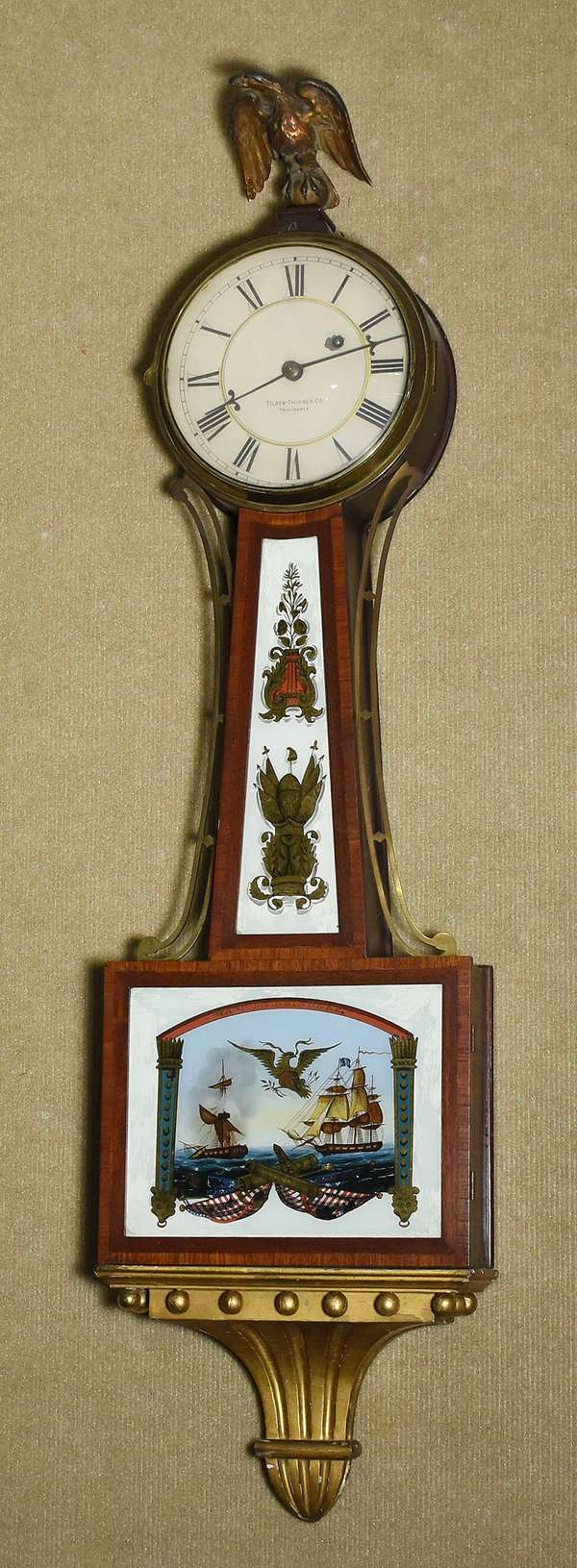 "ANTIQUE TILDEN & THURBER PROVIDENCE R.I. BANJO CLOCK. Reverse painted eglomise tablets, naval door tablet inscribed ""Wasp & Reindeer"", weight driven, 40"" H X 10 1/2"" W. Condition: original naval painted tablet has some flaking (see images) both case sides with scratches, some gilt loss on simulated bracket."