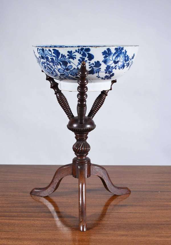 "EARLY DELFT BOWL AND PERIOD BOWL STAND. Well turned and carved mahogany Queen Anne bowl stand ca. 1780-1800, with an early blue and white Delft pottery bowl. Stand 15.5"" H - Bowl 10"" dia. Condition: stand with repair to leg and missing ball finial termination on upper support. Bowl has chipping along rim and foot rim."