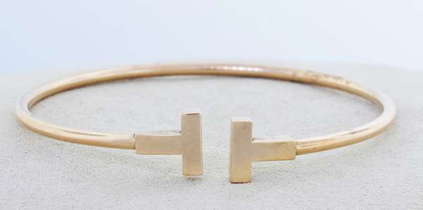 """TIFFANY & Co. """"T"""" 18KT YELLOW GOLD NARROW WIRE BRACELET.  The T's are 9.5 mm wide, 6 inch inner diameter, 8.7 grams.  Good condition, normal wear- New bidders to Smiths - Payment for this lot must be made with Cash, Certified Check or Wire Transfer. NO CREDIT CARDS or Pay Pal accepted. Items will be held by Smiths until payment has cleared."""