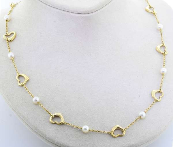 TIFFANY & CO. ELSA PERETTI 18KT YELLOW GOLD OPEN HEART PEARL NECKLACE.  The necklace is 16 inches long , includes a gold filled 5 3/4 inch extension, 9, 5 mm white cultured pearls with rose overtone, heart clasp w/ figure eight safety, 12.3 grams.  Very good condition - New bidders to Smiths - Payment for this lot must be made with Cash, Certified Check or Wire Transfer. NO CREDIT CARDS or Pay Pal accepted. Items will be held by Smiths until payment has cleared.