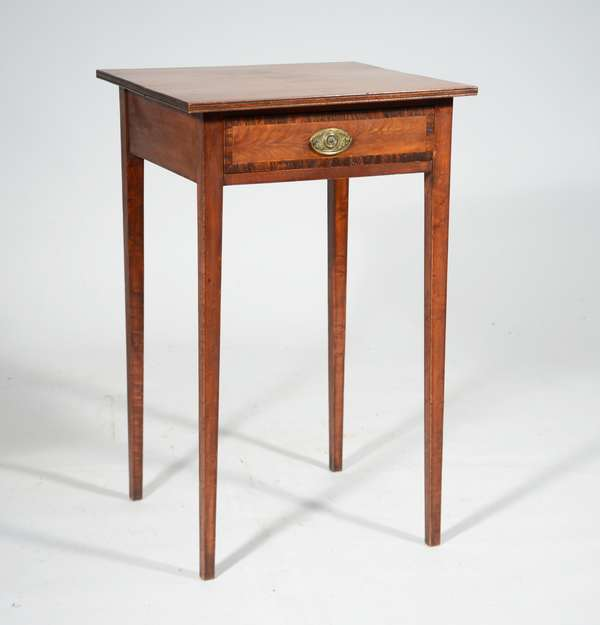 """FINE FEDERAL NH ONE DRAWER STAND CA 1810-20. A very desirable example with slender proportions, birch top with grooved edge, dovetailed drawer with banded and feathered birch inlay and original oval brass, delicate maple tapered legs, 28.5""""H x top 18""""W x 17.5""""D. Condition: very good"""