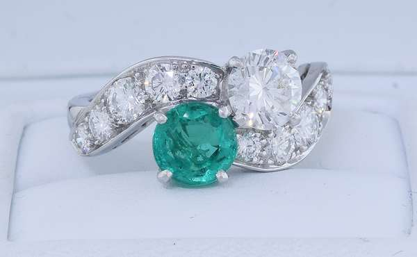 TIFFANY & CO. EMERALD AND DIAMOND PLATINUM RING.  Ladies bypass style iridium platinum ring set with approx. .80 ct. round brilliant cut emerald and approx. .85 ct. round brilliant cut diamond, H-VS, very good cut, accented by approx. .70 ct. tw. round brilliant cut diamonds, G-H-VS, very good cut, sz. 6, 6.7 gr.  Condition: good - New bidders to Smiths - Payment for this lot must be made with Cash, Certified Check or Wire Transfer. NO CREDIT CARDS or Pay Pal accepted. Items will be held by Smiths until payment has cleared.
