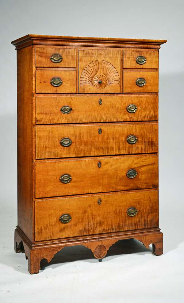 """NH CHIPPENDALE TIGER MAPLE TALL CHEST, DAVID YOUNG.  Top single drawer to simulate 5 small drawers, center with stylized fan carving above 4 long graduated drawers on bracket base with center carved pinwheel drop, all in strong tiger maple. 58""""H x 36""""W x 18"""", Condition: older refinish, replaced brass."""