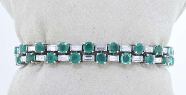 TIFFANY & CO. SIGNED AND NUMBERED PLATINUM EMERALD AND DIAMOND BRACELET.  Iridium platinum bracelet set with alternating round brilliant cut medium slightly bluish green emeralds, approx. 7.0 ct. tw.  separated by baguette cut diamonds, approx. 7.0 ct. tw., G-H-VS, 6 5/8 in. long, 8 mm wide, 44.9 gr.  Good condition, normal wear, (emeralds have small chips and abrasions). - New bidders to Smiths - Payment for this lot must be made with Cash, Certified Check or Wire Transfer. NO CREDIT CARDS or Pay Pal accepted. Items will be held by Smiths until payment has cleared.