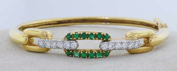 DAVID WEBB 18K GOLD, PLATINUM, DIAMOND AND EMERALD BANGLE. A yellow gold chain link motif bracelet, that is topped with platinum and set with approx. 1 ct. tw. round brilliant cut diamonds, G-H-VS, very good cut, and approx. .75 ct. tw. round brilliant cut medium dark green emeralds, signed, 6 in., 22.6 gr. Condition: good - New bidders to Smiths - Payment for this lot must be made with Cash, Certified Check or Wire Transfer. NO CREDIT CARDS or Pay Pal accepted. Items will be held by Smiths until payment has cleared.