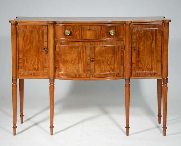 """DIMINUTIVE FEDERAL BOSTON MAHOGANY SIDEBOARD, CA. 1810: a well made mahogany sideboard, a single board mahogany top, swell front, cookie corners on delicate reeded legs with original brass.40""""H x 56""""L x 17""""D Condition: some shrinkage cracks, older refinish, original brass"""