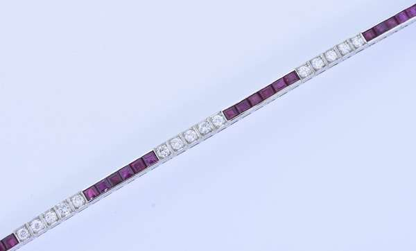 TIFFANY & CO. RUBY AND DIAMOND PLATINUM LINE BRACELET.  Lady's iridium platinum 3.5 mm wide bracelet set w/ approx. 2.0 ct. tw. round brilliant cut diamonds, G-H-VS and approx. 4.0 ct. tw. square step cut medium dark red rubies, 7 in. long, 21.9 gr.  Condition: Good - New bidders to Smiths - Payment for this lot must be made with Cash, Certified Check or Wire Transfer. NO CREDIT CARDS or Pay Pal accepted. Items will be held by Smiths until payment has cleared.