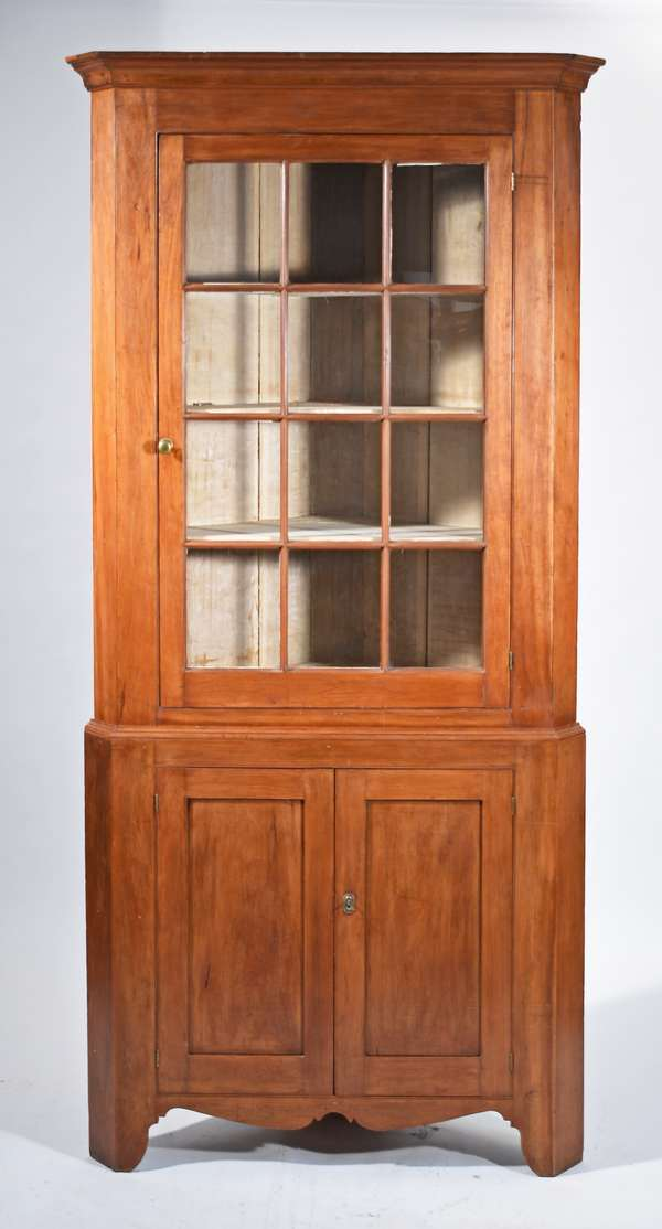 """FEDERAL PA CHERRY 2 PART CORNER CUPBOARD CA 1820. A desirable form with 12 light glass door top, base with 2 panel doors on high cut out base, white washed painted interior, exterior with older pleasant cherry wood refinish, 91""""H x 42""""W, Condition: nicely refinished, some glass panes old replacements, with key."""