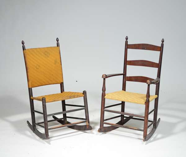 """TWO 19TH C. CHILD'S SHAKER ROCKERS: ladder back arm example stamped  #1 on back splat with three ladder backs, mushroom capped arms, replaced taped seat, in original finish with Mt. Lebanon stamp on inside of rocker 29""""H x 17""""W  ; Armless example has original taped seat and back in old stain 29""""H x 15""""W with some wear and on inside of proper left front leg,  there is a sliver of wood missing"""
