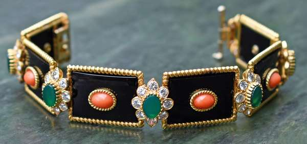 SIGNED AND NUMBERED VAN CLEEF & ARPELS 18K ONYX PANEL BRACELET W/ CORAL, GREEN QUARTZ AND DIAMONDS. Six black onyx panels are set with 5x7 mm oval coral cabochons separated by 5x7 mm buff top dyed green quartz surrounded by approx. 7.0 ct. tw. round brilliant cut diamonds, 7 1/2 in. long, 59.9 gr. Very good condition - New bidders to Smiths - Payment for this lot must be made with Cash, Certified Check or Wire Transfer. NO CREDIT CARDS or Pay Pal accepted. Items will be held by Smiths until payment has cleared.