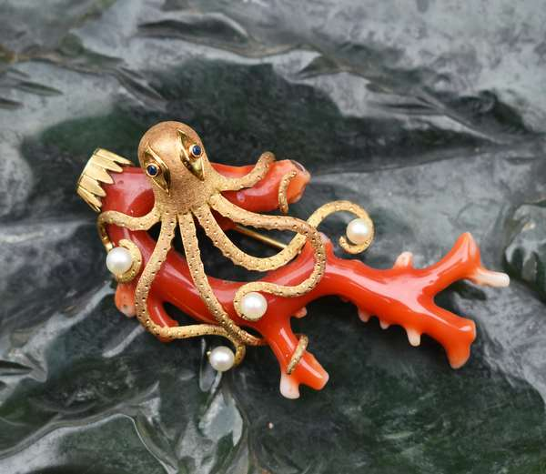 18KT YELLOW GOLD CORAL OCTOPUS BROOCH. Whimsical octopus with blue sapphire eys, approx. .04 ct. tw. plays with four cultured white pearls, 4 mm, good luster, 2 3/4 in. long by 1 1/2 in. wide, stamped 750, trombone catch, 25 grams. Good condition. - New bidders to Smiths - Payment for this lot must be made with Cash, Certified Check or Wire Transfer. NO CREDIT CARDS or Pay Pal accepted. Items will be held by Smiths until payment has cleared.