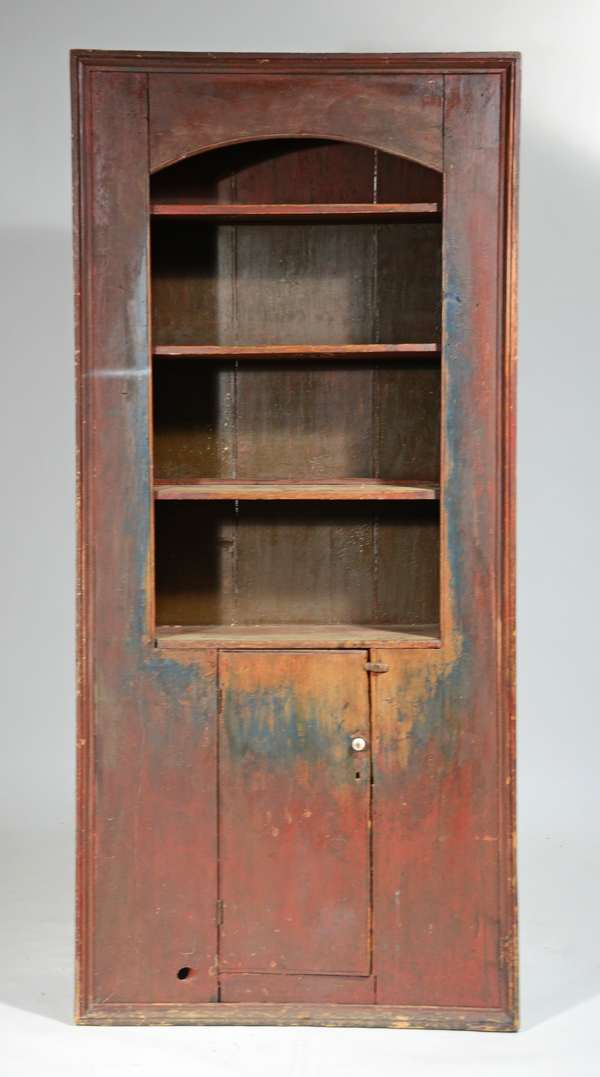 """18TH C. PAINTED COUNTRY FLOOR CUPBOARD: open arched top with three shelves, single plank door on bottom, all encased with picture frame moulding, in an old red, blue/grey painted surface. 81""""H x 38""""W x 14""""D. Condition: paint and edge wear throughout, porcelain pull is an old replacement, commensurate with age and use"""
