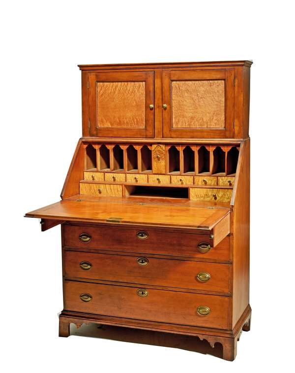 """NH FEDERAL LADIES SECRETARY, CA. 1800: Made in two parts; upper section with two birdseye maple panel doors:  the base in birch with a slant lid opening to reveal a birdseye maple pinwheel carved interior and four graduated drawers below on a bracket base, with original brass. 66""""H x 42""""W x 19.5""""D.  Condition: some minor repairs, very clean. Provenance - Northeast Auctions 2001"""