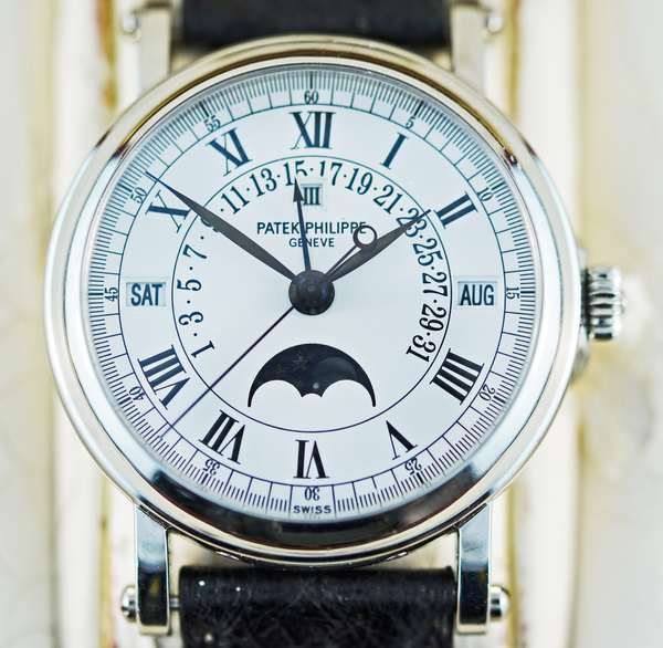 PATEK PHILIPPE PLATINUM PERPETUAL CALENDAR WRIST WATCH. Self-winding automatic watch, features a 36mm platinum case surrounding a white dial on a black alligator band with a platinum Calatrava Cross deployant buckle. Functions include hours, minutes, seconds, day, date, month, perpetual calendar, and moon phase.  This watch and band is accompanied by upholstered wooden box, outer box, purchase/information documents, and leather document holder.  Condition: Alligator band shows some signs of weathering/fading, and has small amounts of box interior upholstery adhered.  Interior of box upholstery does show flaking and cracking.  Box itself, outer box, and documents look to be in great condition.  Leather document holder shows signs of weathering on the exterior. - New bidders to Smiths - Payment for this lot must be made with Cash, Certified Check or Wire Transfer. NO CREDIT CARDS or Pay Pal accepted. Items will be held by Smiths until payment has cleared.