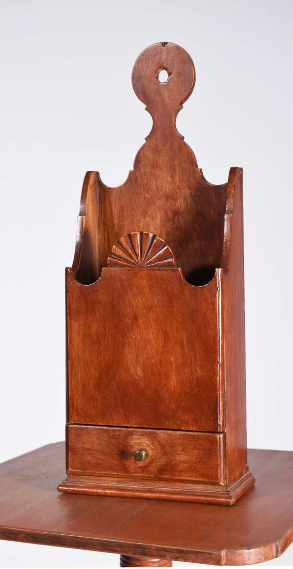 """18TH C. NEW ENGLAND FAN CARVED PIPE BOX; an exceptional form with lollipop handle and nicely scrolled detail, center facade has a fan carving, with a dovetailed drawer on a molded base, a red stained surface and traces of older blue paint on the back 17.5""""H x 7""""W x 3.5""""D Condition: structurally good, wear commensurate with age"""