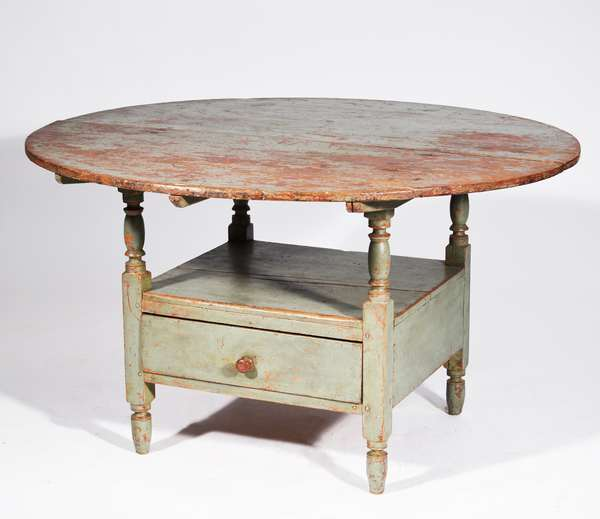 """18TH C. PAINTED ROUND TOP HUTCH TABLE - Choice example with blue/green paint over red, two board removable round top, bottom section has good turnings and one dove tailed drawer, peg construction 27""""H x 46""""Dia. Condition: structurally sound, with shrinkage, some cracks, worn blue/green paint over earlier worn red paint, with castors (in drawer)"""