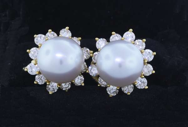 SOUTH SEA PEARL & DIAMOND GOLD CLIP EARRINGS.  The 18 karat yellow gold round earrings set with 11 mm white pearls with very good luster that are surrounded by approx. 2.0 ct. tw. round brilliant cut diamonds, G-VS, very good cut, 16 mm (approx. 1/2 in.) in diameter, 12.6 gr.  Very good condition. - New bidders to Smiths - Payment for this lot must be made with Cash, Certified Check or Wire Transfer. NO CREDIT CARDS or Pay Pal accepted. Items will be held by Smiths until payment has cleared.