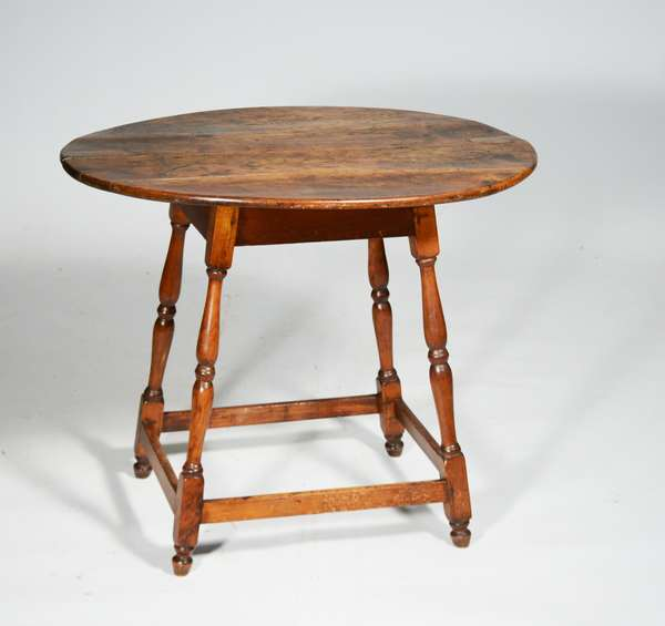 """18TH C. NEW ENGLAND MAPLE STRETCHER BASE TAVERN TABLE. an oval two board maple top, splayed sausage turned legs box stretcher base and returned feet, old finish, 26.5""""H x 31""""L x 26.5""""D. Condition top with cracks other repairs."""