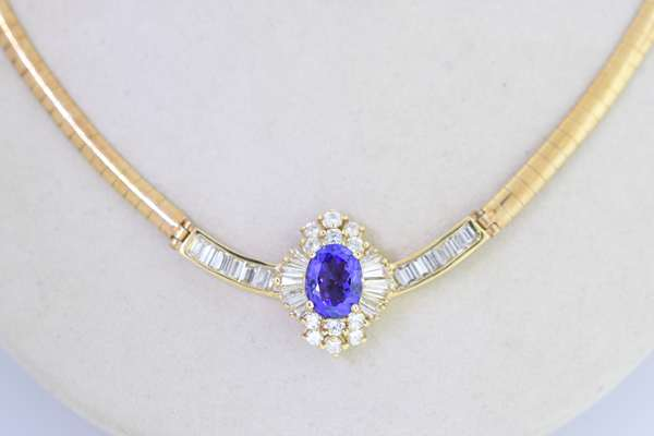 14KT YELLOW GOLD TANZANITE & DIAMOND NECKLACE.  Approx. 2.78 ct. oval brilliant cut dark violetish blue tanzanite, eye clean, accented by approx. 3.0 ct. tw. round brilliant, tapered and straight cut baguette diamonds, 4 mm half round omega chain,  17 1/2 inches long, 25.5 grams. Very good condition. - New bidders to Smiths - Payment for this lot must be made with Cash, Certified Check or Wire Transfer. NO CREDIT CARDS or Pay Pal accepted. Items will be held by Smiths until payment has cleared.
