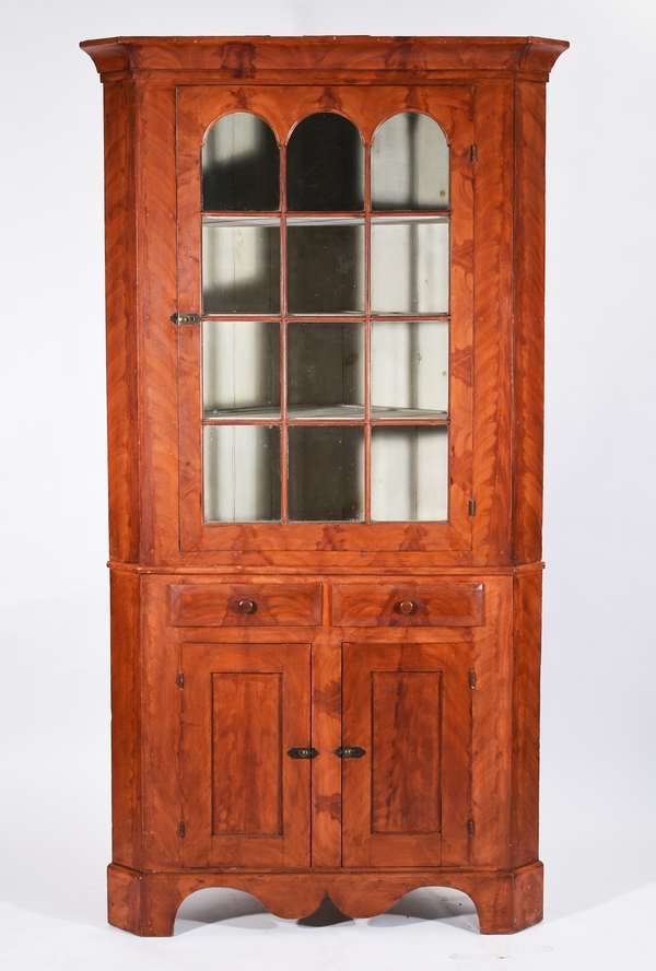 """FINE PAINT DECORATED 19TH C. CORNER CUPBOARD. In two parts, top section with applied moulded cornice, single arched glass door.  Base has two dovetailed drawers above two paneled doors on a scrolled, applied bracket brace.  Original grain painted decoration over pine. 90""""H x 44""""W.  Condition: Fine condition, original glass top and original glass doors.  Original paint.  Structurally sound."""