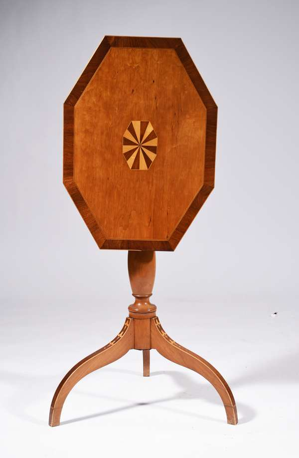 FEDERAL HIGHLY INLAID CANDLESTAND CA 1810: an attractive cherry tilt top candle stand with a coffin tilting top oval alternating inlaid center with mahogany cross banded top, a baluster turned standard on spider legs with bellflower inlays within mahogany veneers. Condition refinished block repaired.