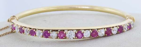 """14K GOLD RUBY AND DIAMOND BANGLE BRACELET: set with 10 rubies and 11 diamond the largest approx. .30 ct total weight approx. 1.5 ct, 13.7 grams, 2.25""""H x 2.5""""L. Condition good.- New bidders to Smiths - Payment for this lot must be made with Cash, Certified Check or Wire Transfer. NO CREDIT CARDS or Pay Pal accepted. Items will be held by Smiths until payment has cleared."""