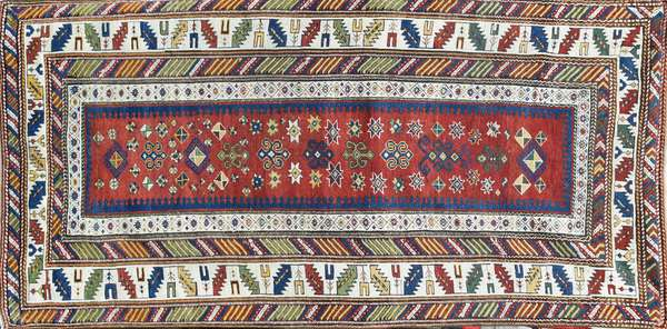 """ANTIQUE SHIRVAN ORIENTAL SCATTER RUG. Vibrant and attractive with bold red, ivory, blues and greens. 3'9"""" x 7'9"""". Condition: some stitched repairs and wear commensurate for age"""